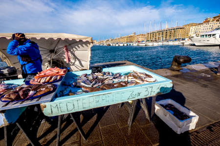 Marseille, France - March 6, 2017: Fish seller at the fish market at the old port, Vieux Port, Marseille, Bouches-du-Rhone, Provence-Alpes-Cote dAzur, Southern France, France, Europe