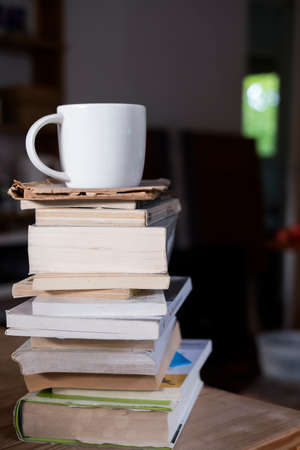 white cup with cappuccino coffee on top of a small tower made up of books inside a hipster room