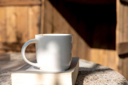 white cup with cappuccino coffee and books on an old table with a background of old rustic woods