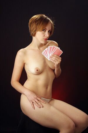 A beautiful young woman wearing only panties holds a hand of playing cards. Stock Photo - 6820394