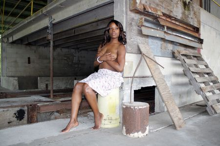 A beautiful young black woman sits topless amidst the clutter of a long-abandoned warehouse and loading facility. Stock Photo - 6877741