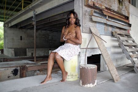 A beautiful young black woman sits topless amidst the clutter of a long-abandoned warehouse and loading facility.