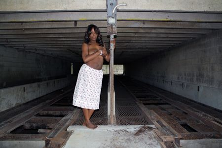 A beautiful young black woman stands topless in front of a rail at a long-abandoned warehouse and loading facility.