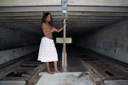 A beautiful young black woman stands topless in front of a rail at a long-abandoned warehouse and loading facility. photo