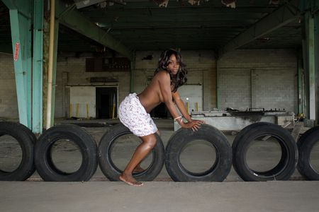 A beautiful young black woman sits topless on old automobile tires amidst the clutter of a long-abandoned warehouse and loading facility.