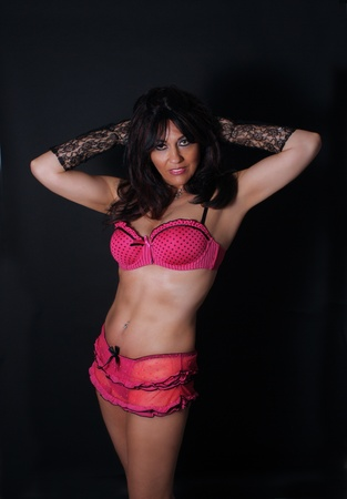 musculature: A lovely mature woman with remarkable abdominal musculature and wearing pink lingerie. Stock Photo