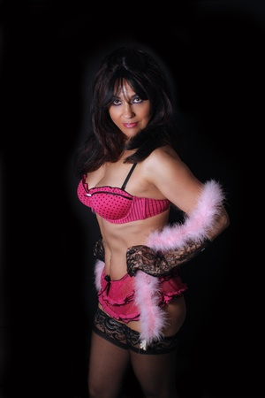 A lovely mature woman with remarkable abdominal musculature and wearing pink lingerie with a feather boa.