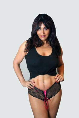 abbreviated: A lovely mature woman with remarkable abdominal musculature and wearing a black abbreviated tank top with black panties.
