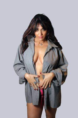 durchbohrt: Eine sch�ne Frau tr�gt eine offene Button-down Hemd mit schwarzen H�schen.