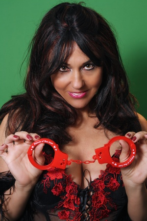 A close-up of a sexy woman dressed in lingerie, holding a pair of plastic handcuffs on which are printed the words,
