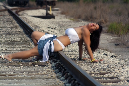 auburn hair: A lovely woman with auburn hair relaxing in the sun on a railroad track. Stock Photo