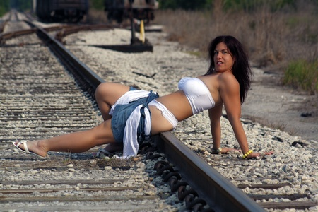 railway transportation: A lovely woman with auburn hair relaxing in the sun on a railroad track. Stock Photo