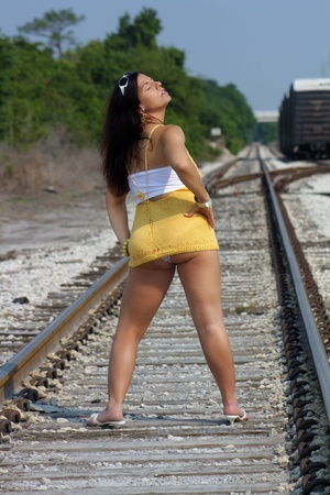 ass jeans: A lovely woman with auburn hair standing on a railroad track with her back to the camera.