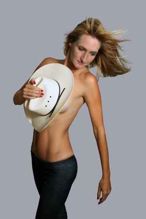 A lovely topless blonde covered by a white cowboy hat.