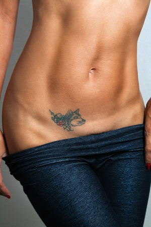 A sexy, toned female abdomen with a canine tattoo.