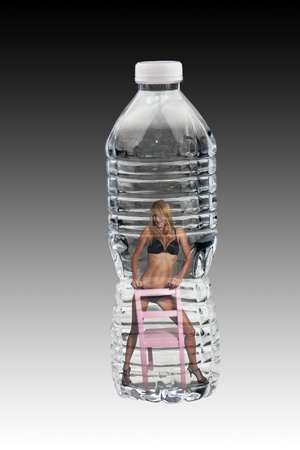 A lovely well-toned blonde wearing midnight-blue panties and bra, standing stradle on a pink, wooden chair, inside a bottle of water. photo