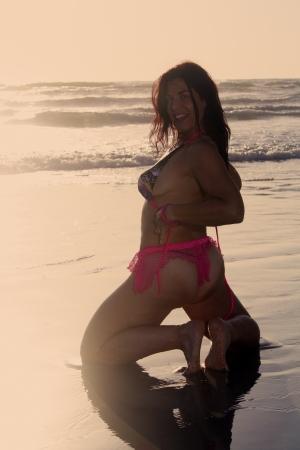 A beautiful woman kneeling on the beach at sunrise. photo