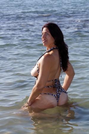 donna in ginocchio: Una bella donna inginocchiata nel surf in spiaggia al sorgere del sole. Archivio Fotografico
