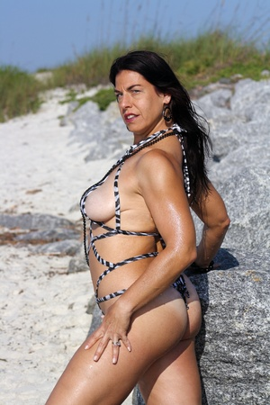 A beautiful woman wearing a sexy swimsuit at the beach. photo
