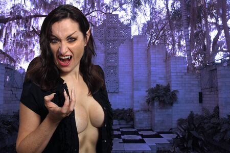 A beautiful, busty, but deadly brunette female vampire in front of her lair. Stock Photo