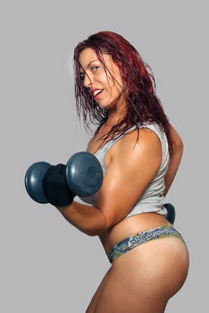 A sexy, busty redhead working out with weights.