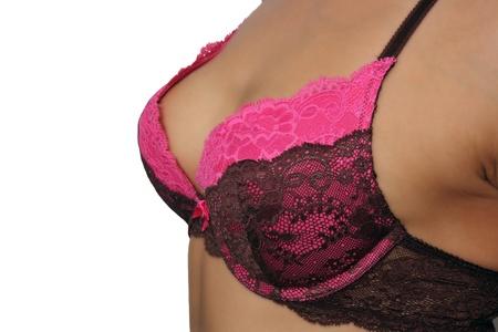 A close-up of a female chest wearing a pretty pink and black bra. Standard-Bild