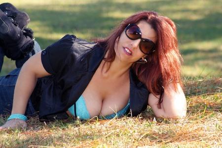 セクシー、官能的な赤毛明るい、晴れた日に屋外草にあります。