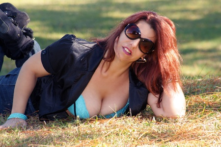A sexy, voluptuous redhead lies in the grass outdoors on a bright, sunny day.