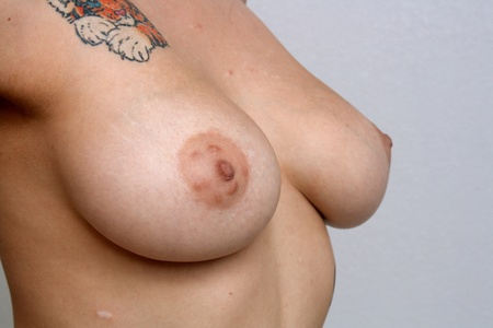 A close-up of large female breasts, completely unretouched and unedited.  Isolated on a textured grey background.