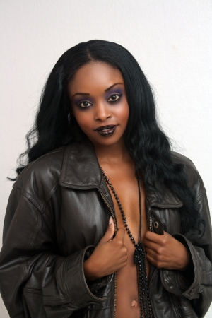 An extraordinarily beautiful, sexy, and dynamic woman wearing a leather jacket unzipped. photo