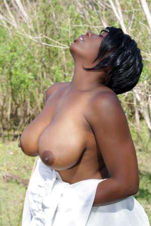 A lovely young, topless model in a tropical forest