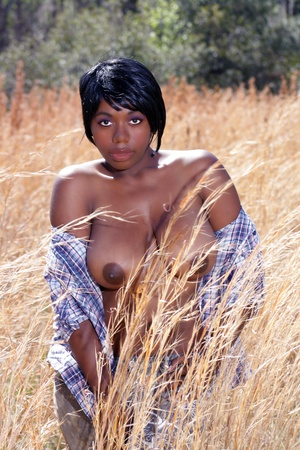 A lovely young, topless model stands in a field of tall grass