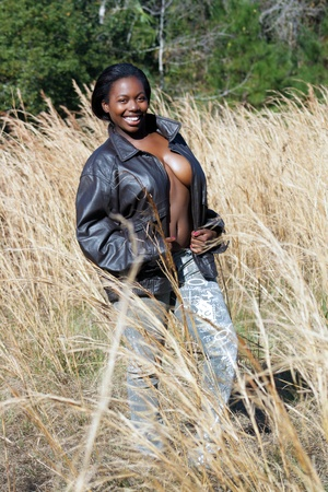 A lovely, black woman outdoors in a field of tall grass