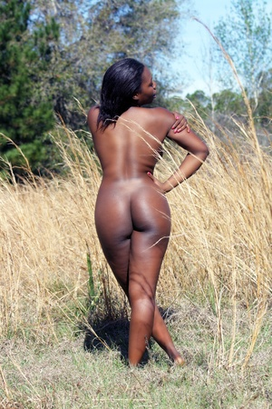 nude ass: A lovely, sexy, nude, black woman standing in tall grass with her back to the camera  Stock Photo