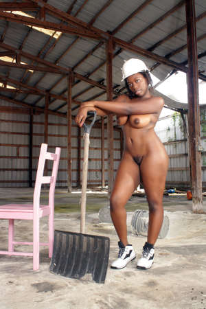 mujer negra desnuda: Una hermosa mujer desnuda negro con un casco blanco con zapatos a juego, se encuentra en medio del desorden de un almac�n abandonado de largo
