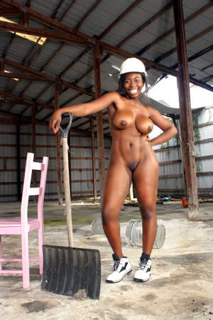 A lovely nude black woman wearing a white hardhat with matching footwear, stands amidst the clutter of a long-abandoned warehouse   Stock Photo