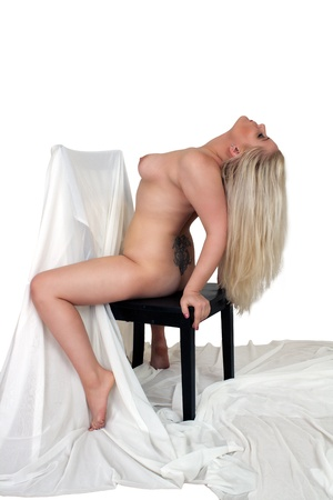 A lovely, sexy, nude young blonde straddles a chair with white sheer fabric   Isolated on a white background with generous copyspace
