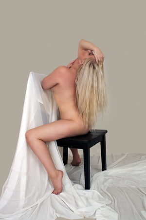 A lovely, sexy, nude young blonde straddles a chair with white sheer fabric   Isolated on a light-gray background with generous copyspace  photo
