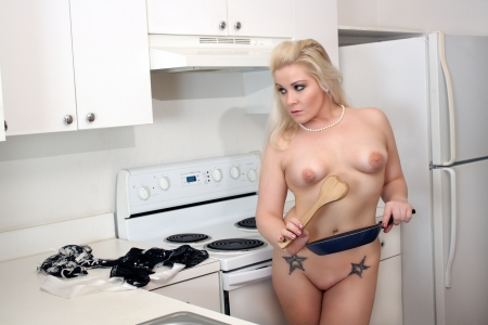 A lovely, sexy, nude young blonde holding a frying pan with a wooden spatula in her kitchen