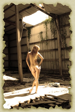 A lovely nude blonde stands amidst the garbage in a long-abandoned warehouse facility