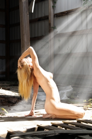 A lovely nude blonde kneels, bathing in sunlight, amidst the garbage in a long-abandoned warehouse facility