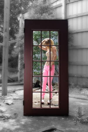 A beautiful blonde seen through a surreal doorway leading to colour in the otherwise monotone environment of a long-abandoned warehouse facility