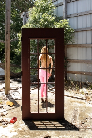 A lovely blonde dressing  or undressing  seen through a freestanding surreal doorway in a derelict, trash-filled environment  photo