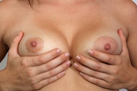 femme se deshabille: Un gros plan de asym�triques seins des femmes, sans retouche. Banque d'images