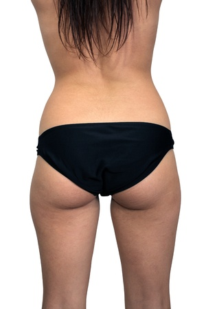 A rear view of a female torso isolated on a white background, unretouched