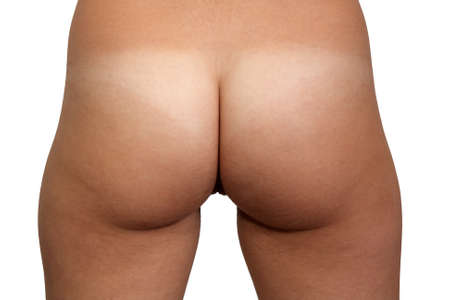 A close-up rear view of nude female buttocks, unretouched
