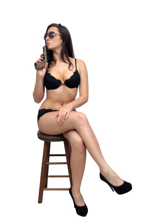 A lovely young brunette sits on a barstool, holding a modern handgun   Isolated on a white background with generous copyspace  photo