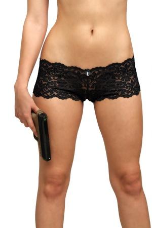 eroticism: A close-up of a modern handgun, held by a female beside her leg