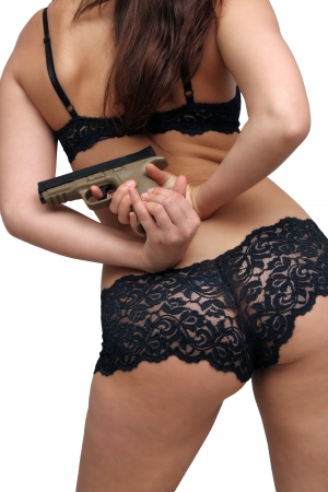 A close-up of a modern handgun, held by a female behind her  photo