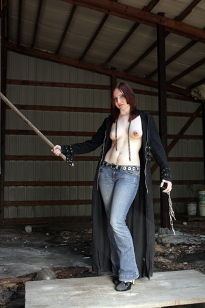 An attractive young redhead wearing jeans, chains, and an open trench coat, stands in an abandoned commercial buidling
